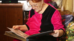 An elderly woman looking photo album Stock Footage