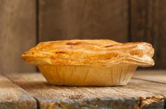 Pie on Wooden Background Shot at Neutral Angle - stock photo