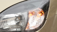 Indicator light blinks in front of the car headlights Stock Footage
