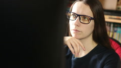 Young girl in glasses sitting at a computer works Stock Footage