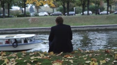 Man Sits On The Bank Of The Canal Stock Footage
