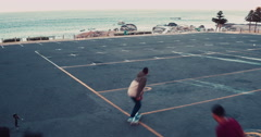 African American skateboarding in seaside parking lot Stock Footage