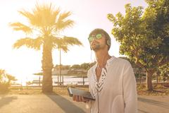 Stock Photo of young man with digital tablet in summertime in casual clothes and sunglasses