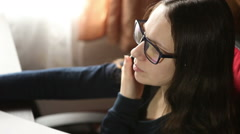 Girl with glasses talking on the phone while sitting at the computer Stock Footage