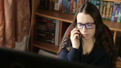 Girl with glasses talking on the phone while sitting at the computer - stock footage