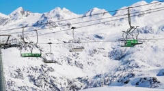 Empty chairlift with snow-covered montains Stock Footage