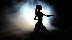 Girl athlete shows power moves. Black. Silhouette. Backlight Stock Footage