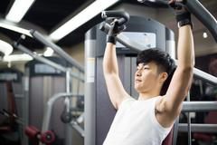 Young handsome man works out in modern gym Stock Photos