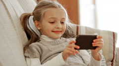 Cute little girl playing with smartphone at home - stock footage