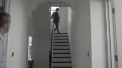 Teenager boy on staircase towards mature adult father - stock footage