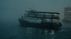 Hong Kong ferry moving away on a foggy day Stock Footage