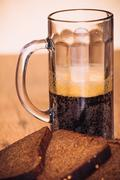 Russian brew in mug and loaf of rye flour on wooden background Stock Photos