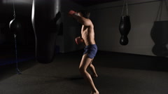 Fury. muscular handsome fighter giving a forceful forward kick during a practise Stock Footage