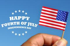 Happy Fourth of July greeting card with american flag in blue sky background - stock photo