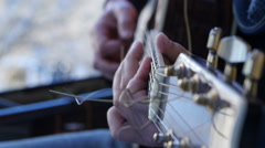 Man playing accoustic guitar outdoors, close up footage Stock Footage