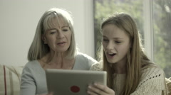 Grand Mother and teenage child at home looking at digital tablet Stock Footage