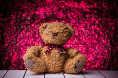 Teddy bear sitting on white wooden floor with nice bokeh background Stock Photos