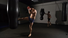 Aggression. muscular handsome fighter giving a forceful forward kick during a Stock Footage