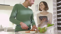 16 70 23 Couple Preparing Healthy Food and using Tablet at Kitchen - stock footage