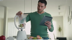 16 70 19 Man using Tablet While does Smoothie - stock footage