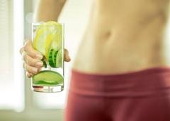 Healthy coctail in the hands of fitness female. - stock photo