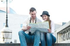 Touristic couple looking at map on the city street - stock photo