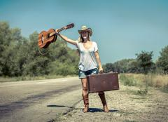 Stock Photo of Cowboy style girl on the road under sunlight