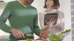 16 70 24 Couple using Tablet at Kitchen Stock Footage