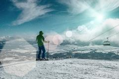 Skier stay on the peak of mountain in sunny day. - stock photo
