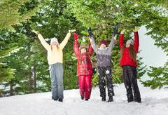 Four children standing in row at the winter forest Stock Photos
