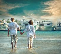 Stock Photo of Couple on the sea beach under sunlight