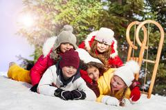 Happy friends laying at the snow in winter forest - stock photo
