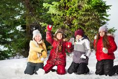 Happy friends playing snowballs at winter forest - stock photo