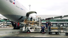 airport workers load cargo to aiplane (or unload from aircraft)  - stock footage