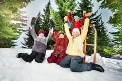 Happy kids resting after winter games in snowdrift - stock photo