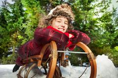 Smiling girl having fun in winter snow on a sledge - stock photo