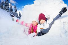 Boy and girl flourish their arms from a snow hole Stock Photos