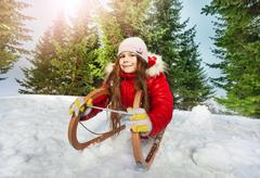 Girl in winter clothes having fun on snow sledge - stock photo