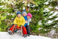 Children little boys and girl slide on sledge Stock Photos