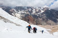 Group of Hikers Walking on Snow and Ice Terrain - stock photo