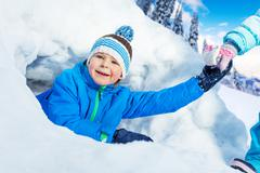 Stock Photo of Boy get pulled out of snow tunnel in park