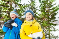Two boys with big chunk of snow in the park Stock Photos