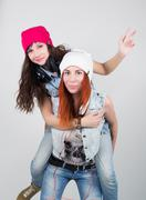 beauty hipster girls indulge, one girl jumped on his back the other - stock photo