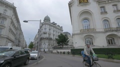 Riding bikes and driving cars in Schwarzenbergplatz, Vienna Stock Footage