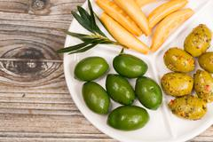 White board with giant  green olives and bread - stock photo