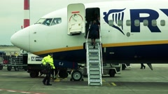 Airplane stands at airport and stewardesses open plane door Stock Footage
