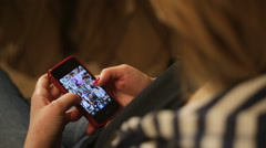 Casual woman using her smartphone at home in the living room Stock Footage
