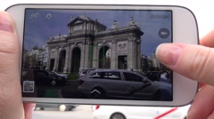 4K Woman take photo mobile phone Alcala Gate traffic car busy Madrid avenue day  Stock Footage