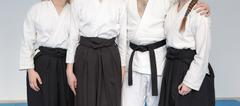 People in kimono and hakama standing on tatami with martial arts master Stock Photos
