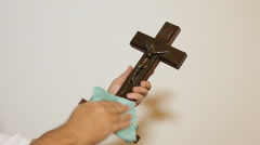 Man cleaning Christian cross with cloth Stock Footage
